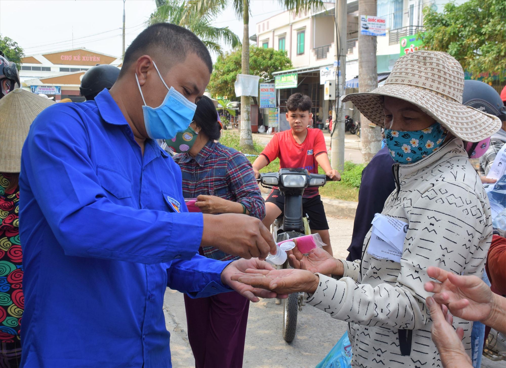 Đoàn viên thanh niên hướng dẫn người dân sử dụng nước sát khuẩn rửa tay nhiều lần trong một ngày để phòng bệnh. Ảnh: THANH THẮNG