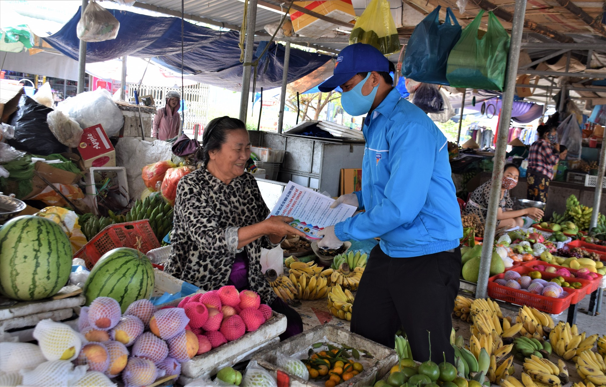 Cán bộ đoàn thanh niên xã Bình Trung, huyện Thăng Bình, phát tờ rơi và tuyên truyền cho tiểu thương tại chợ Kế Xuyên nên đeo khẩu trang tại những nơi công cộng hoặc đông người để phòng chống dịch bệnh Covid-19: Ảnh: THANH THẮNG
