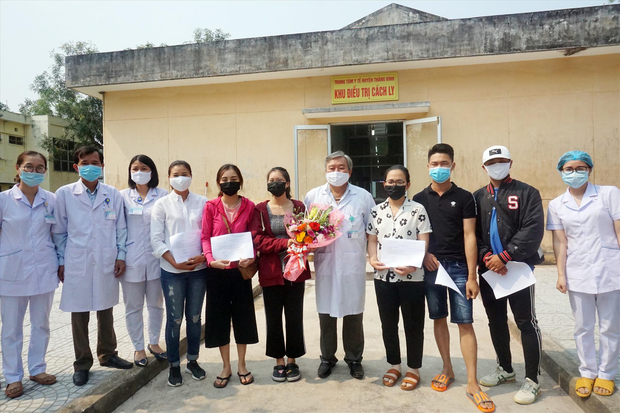 Đại diện Trung tâm Y tế huyện Thăng Bình trao hoa và giấy xác nhận hoàn thành cách ly y tế cho 6 trường hợp cách ly tại đây. Ảnh: BIÊN THỰC