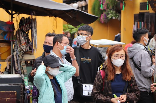 Tourists in Hoi An ancient town with medical masks