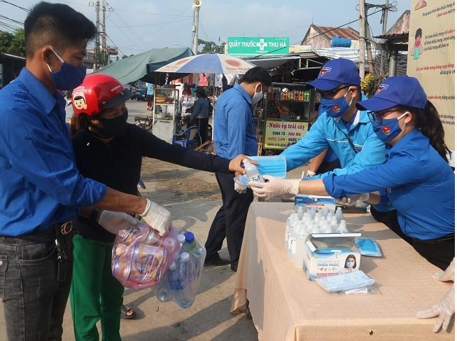 Một người dân mang chai nhựa đổi khẩu trang và nước sát khuẩn mang về.