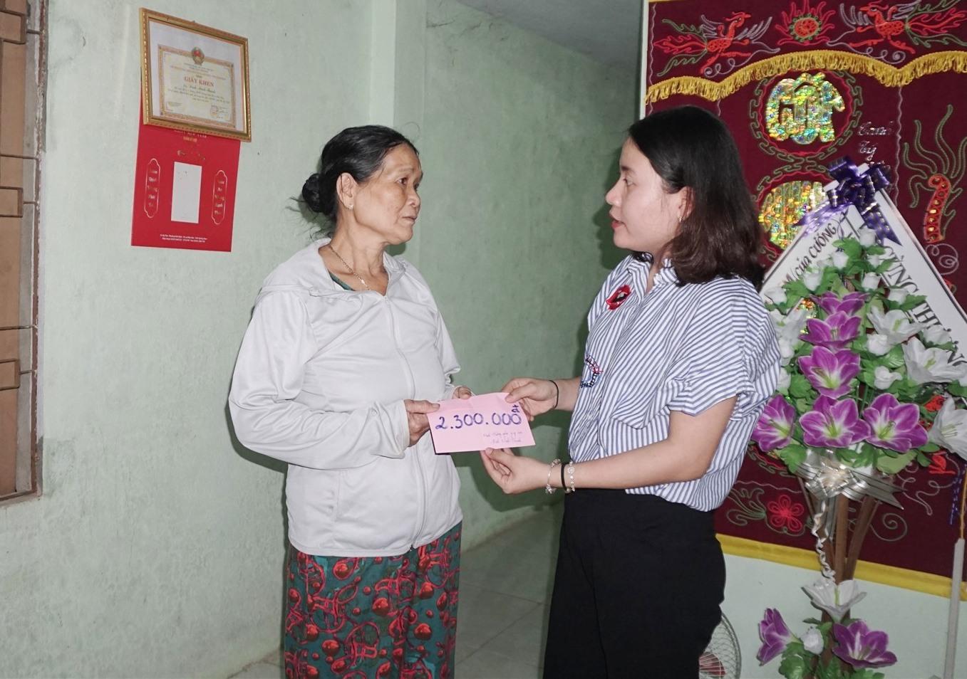 Đại diện gia đình nhận số tiền 2,3 triệu đồng bạn đọc giúp đỡ em Đinh Minh Thạnh. (ảnh: NT)