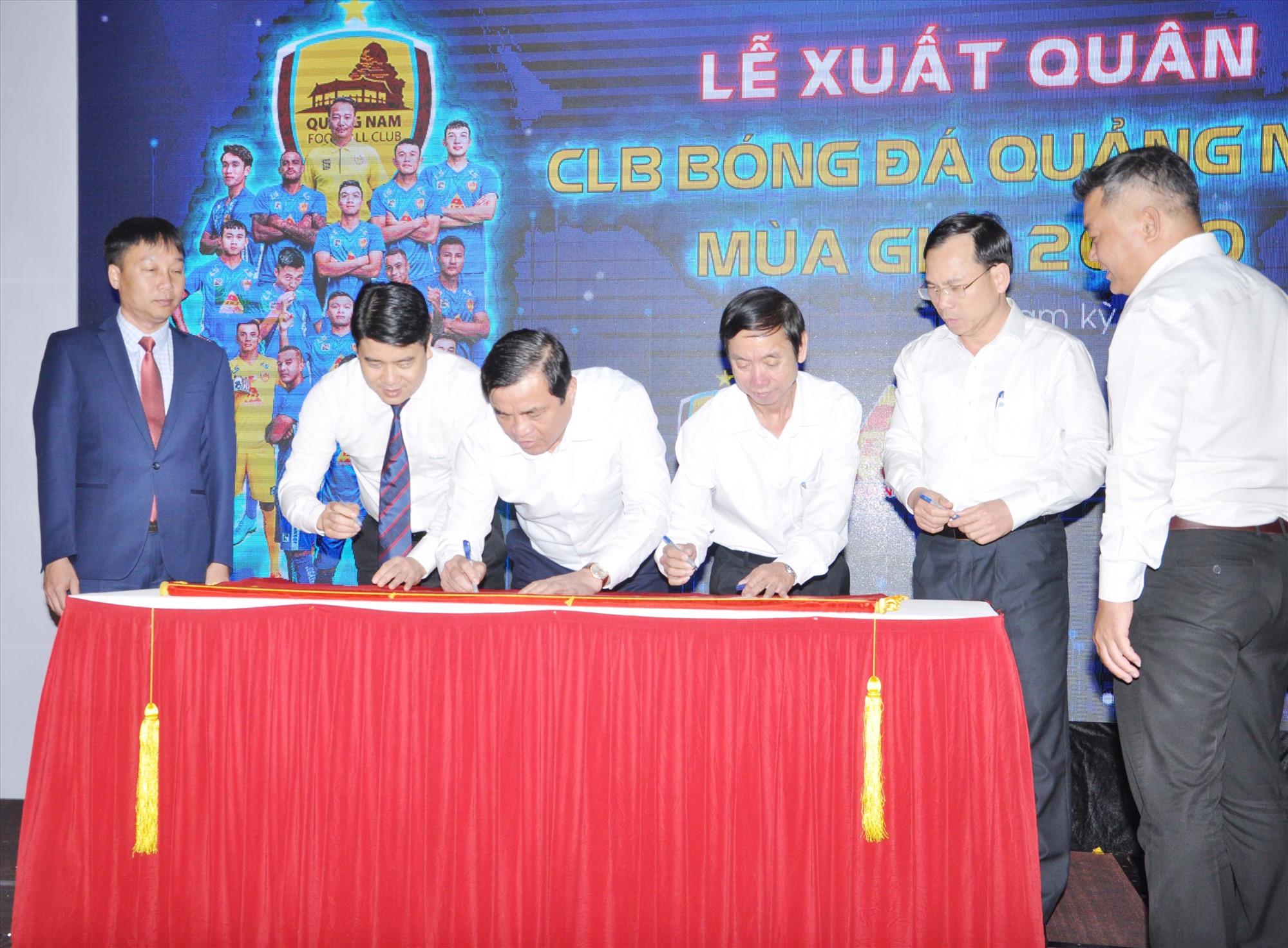 Các đồng chí lãnh đạo tỉnh ký vào cờ xuất quân của UBND tỉnh tặng Câu lạc bộ Quảng Nam. Ảnh: T.V