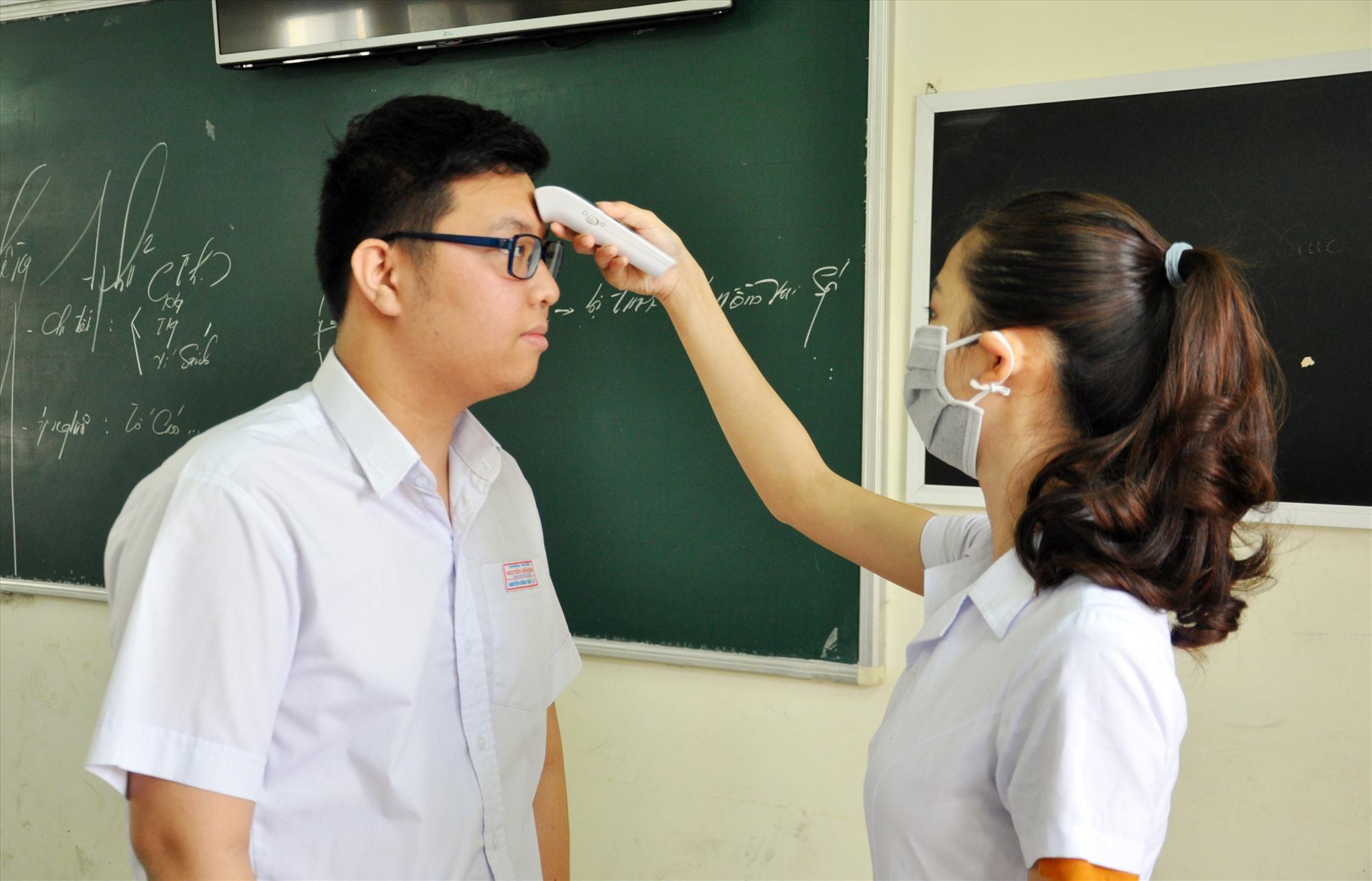 Kiểm tra thân nhiệt HS tại Trường THPT chuyên Nguyễn Bỉnh Khiêm. Ảnh: X.P