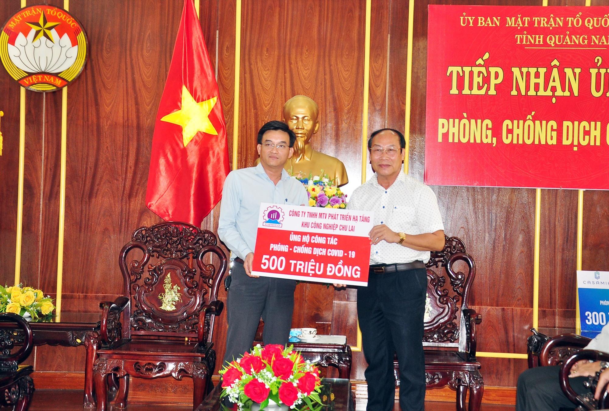 Chủ tịch Ủy ban MTTQ Việt Nam tỉnh Võ Xuân Ca (phải) tiếp nhận nguồn hỗ trợ 500 triệu đồng cho công tác phòng chống dịch Covid-19 từ Công ty TNHH MTV Phát triển hạ tầng Khu công nghiệp Chu Lai. Ảnh: VINH ANH