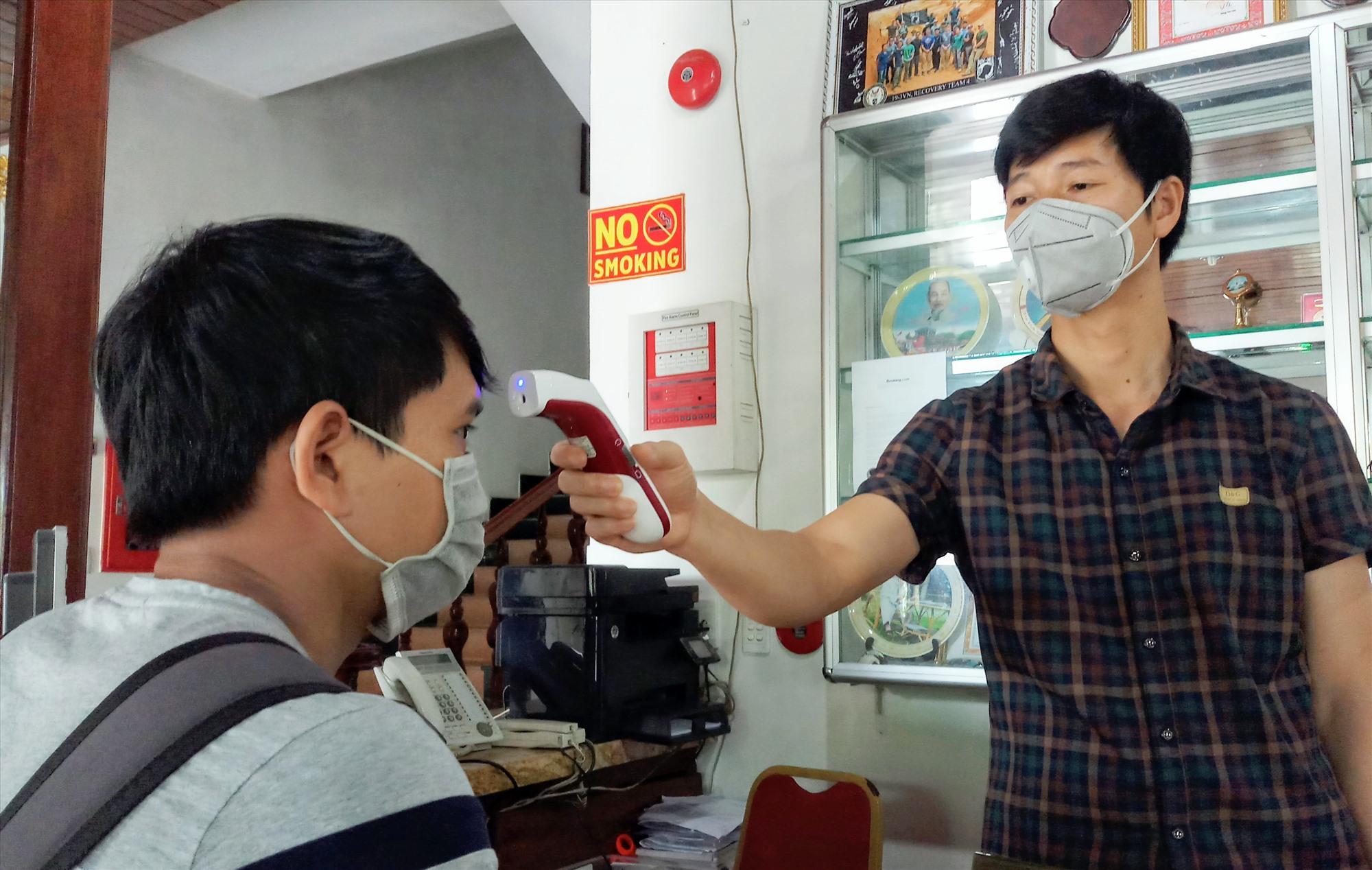 Nhân viên khách sạn Bé Châu Giang (Phước Sơn) tiến hành đo thân nhiệt khách đến đặt phòng lưu trú. Ảnh: ALĂNG NGƯỚC