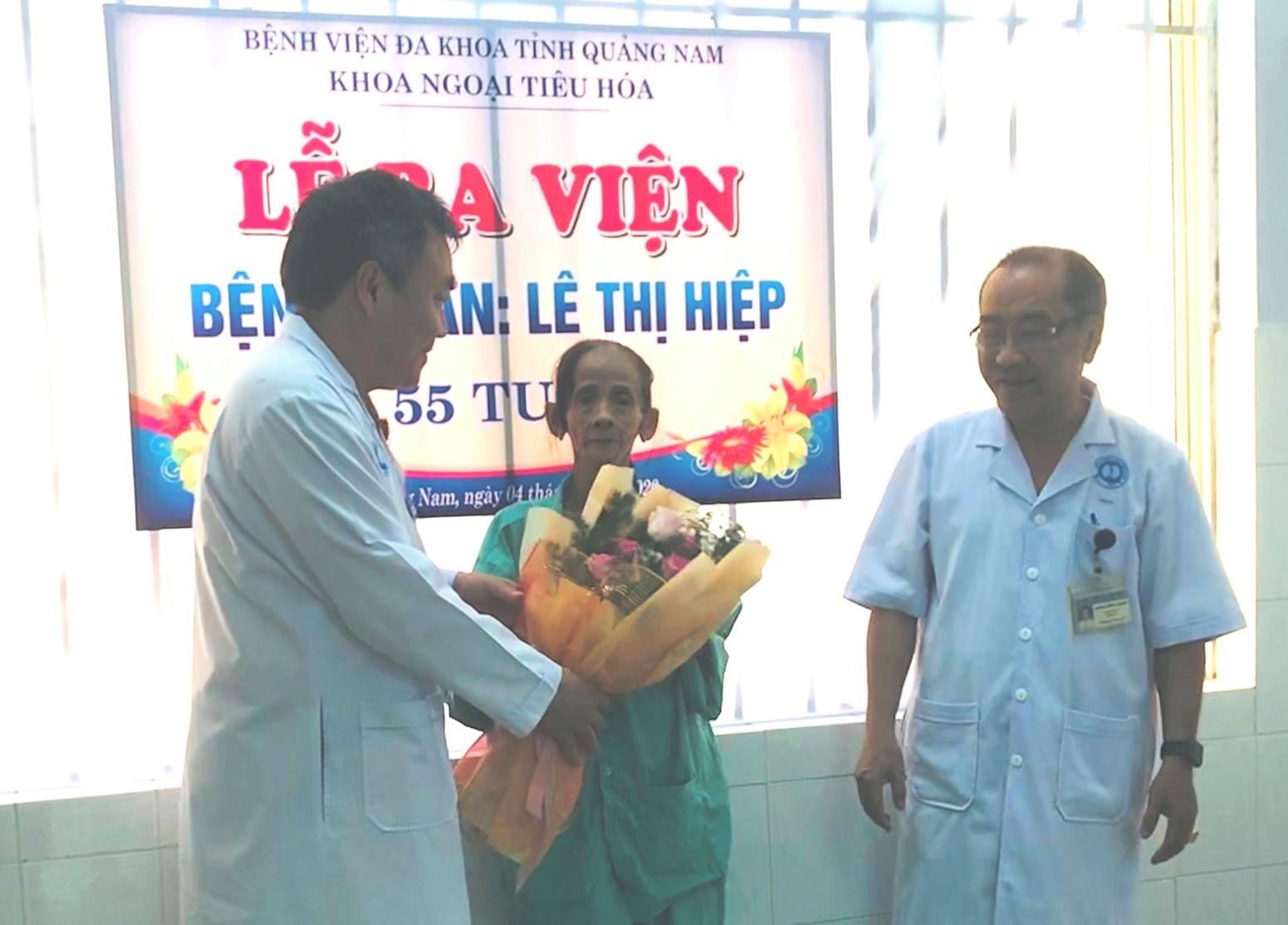 Giám đốc BVĐK Quảng Nam (trái) tặng hoa và trao giấy ra viện cho bệnh nhân. Ảnh: C.N