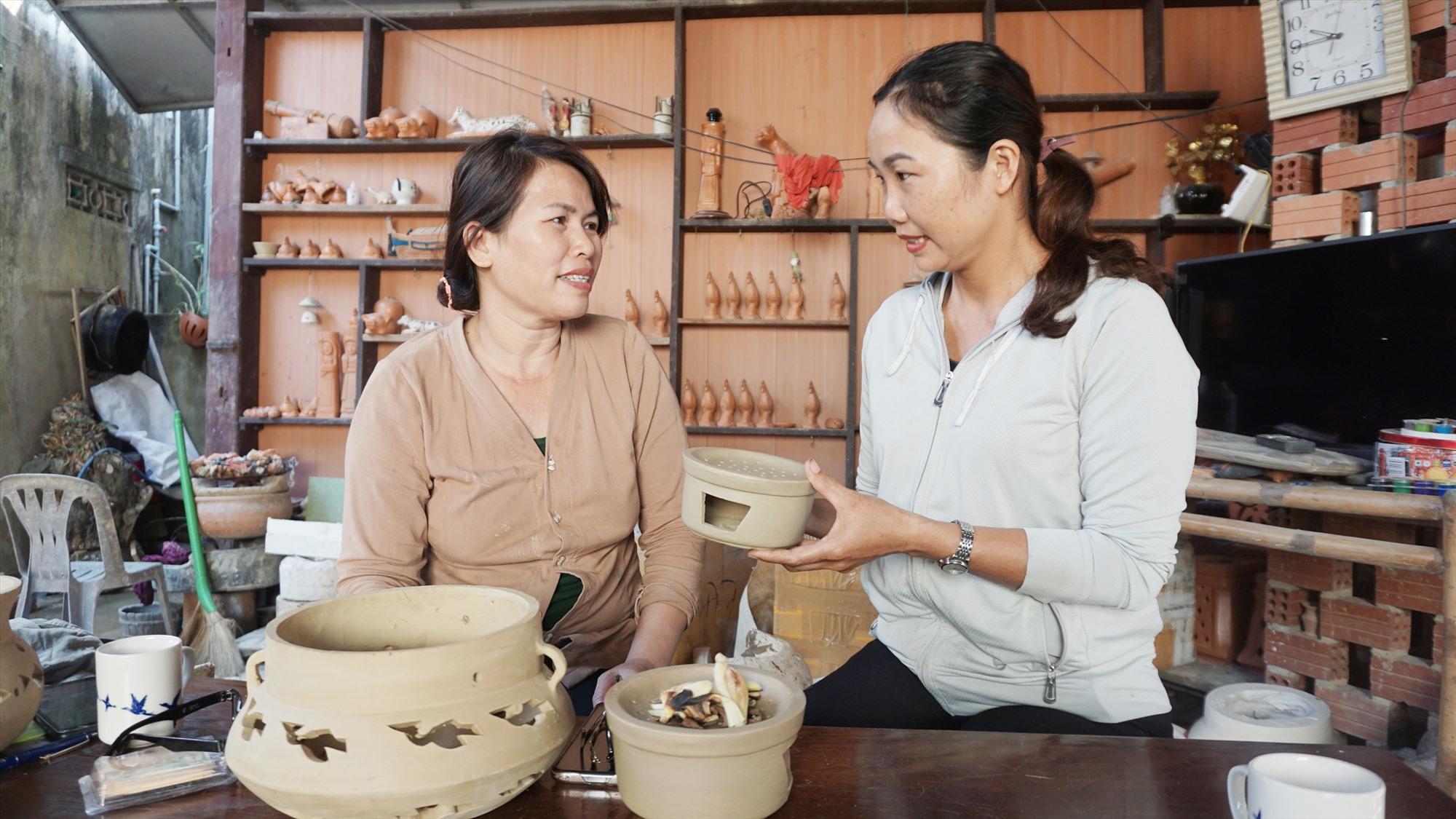 Chị Nguyễn Thị Bích Tuyến (bên trái) với sản phẩm nồi đốt thảo mộc mới hoàn thành. Ảnh: N.TRANG