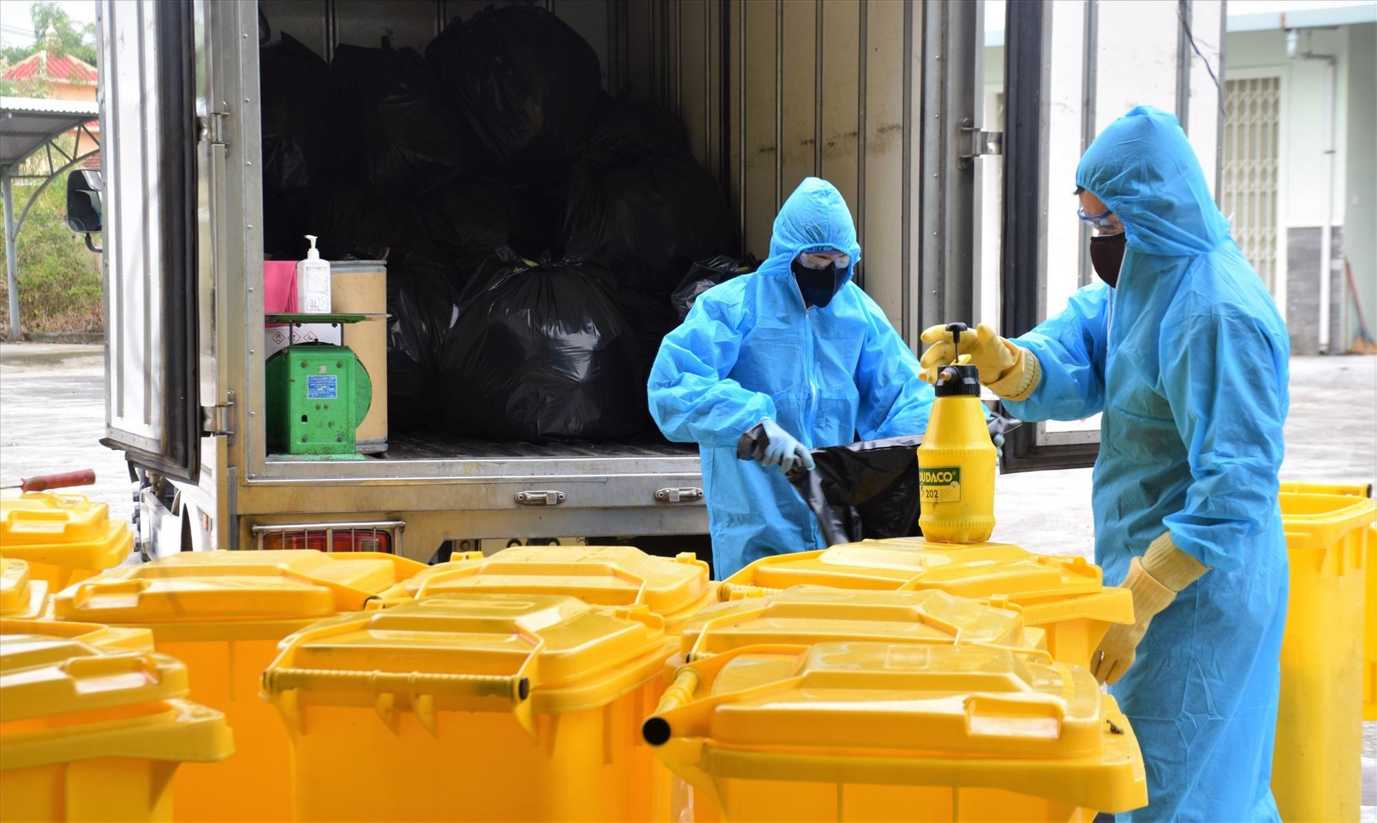 Công nhân mặc đồ bảo hộ khi thu gom rác thải tại khu cách ly tập trung Phòng khám đa khoa Khu công nghiệp Điện Nam Điện Ngọc. Ảnh: THANH THẮNG