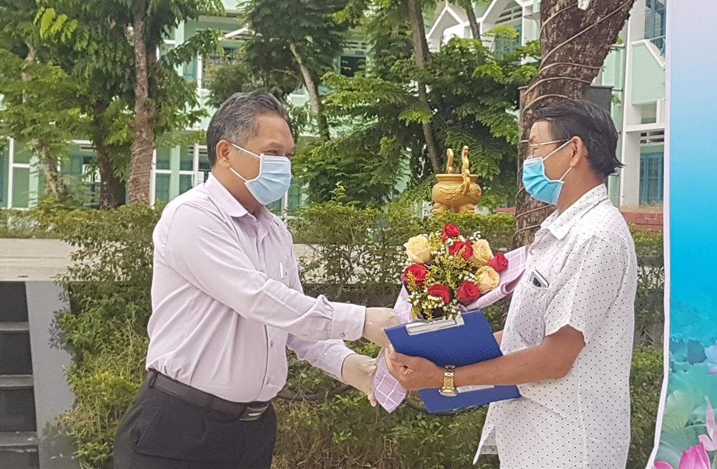 Ông Phùng Văn Huy trao hoa chúc mừng công dân hoàn thành cách ly tập trung. Ảnh: D.L