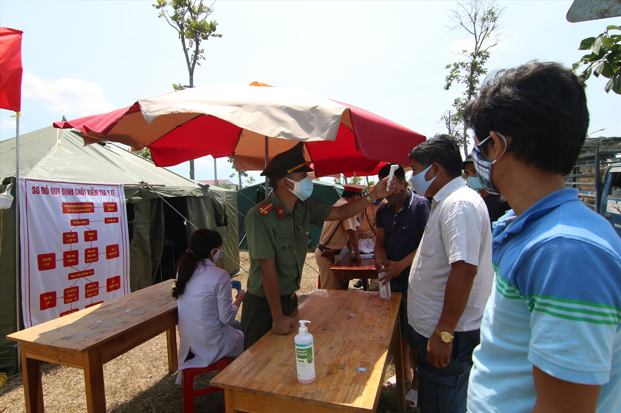 Trung úy Nguyễn Hồng Trung kiểm tra nhiệt độ cho tài xế và các hành khách tại chốt kiểm soát chống dịch Covid-19 Tam Hiệp (Núi Thành). Ảnh: T.C