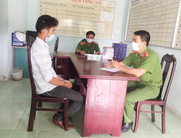 Công an làm việc với đối tượng Phương (trái), người đòi hành hung tổ kiểm soát y tế ở Nông Sơn. Ảnh: T.L