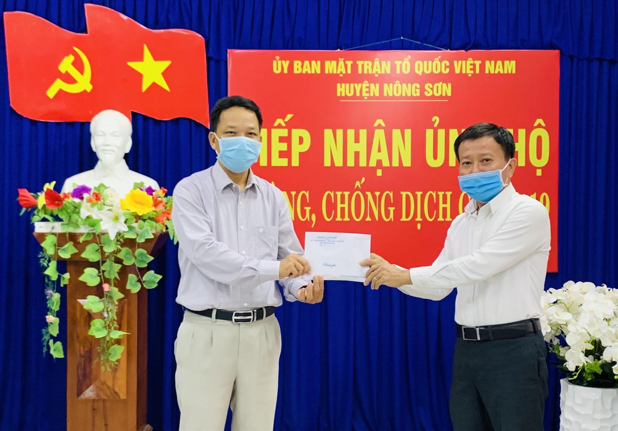 Ông Thái Bình thay mặt cho các doanh nghiệp, nhà hảo tâm trao tiền hỗ trợ cho Ủy ban MTTQ Việt Nam huyện Nông Sơn phục vụ công tác phòng, chống dịch Covid-19. Ảnh: PHAN VINH