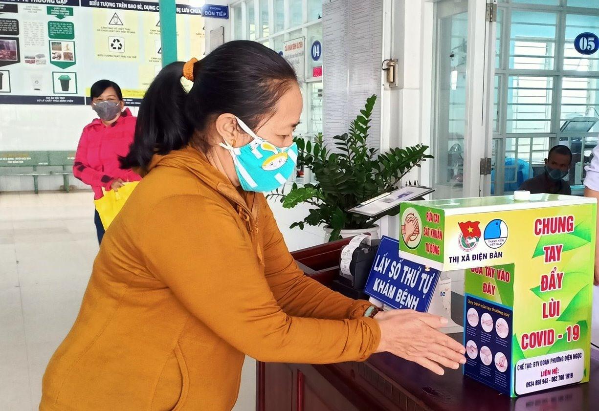 Người dân sử dụng máy rửa tay sát khuẩn tại Bệnh viện Đa khoa khu vực Quảng Nam. Ảnh: T.N