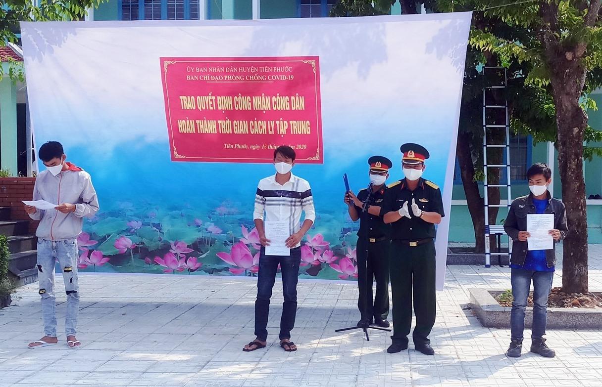 Lãnh đạo Ban CHQS huyện Tiên Phước trao quyết định hoàn thành cách ly tập trung cho 15 công dân. Ảnh: NGUYỄN HƯNG