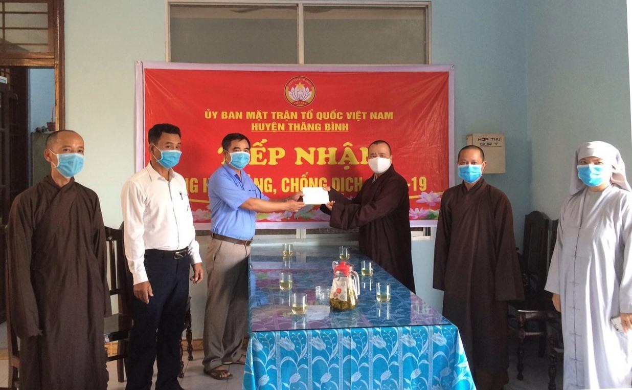 Đại diện Ủy ban MTTQ Việt Nam huyện Thăng Bình tiếp nhận tiền ủng hộ từ đại diện Ban Trị sự Giáo hội Phật giáo Việt Nam huyện