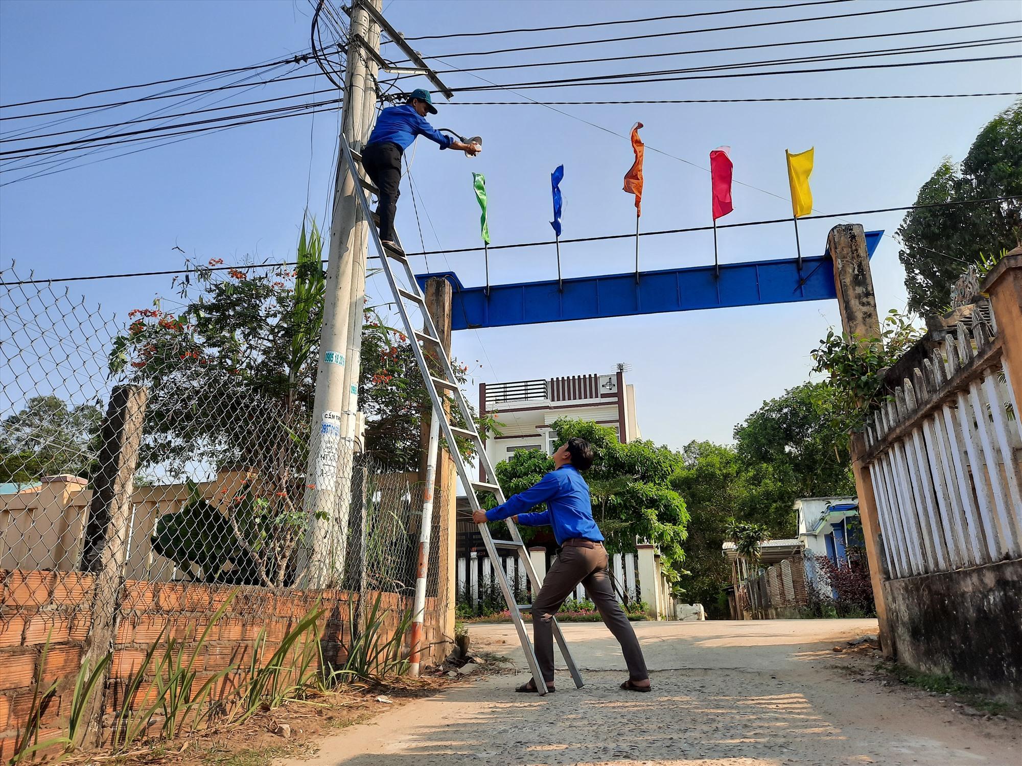 Thanh niên xã Tam Anh Bắc thực hiện lắp đèn đường tại thôn Trà Lý. Ảnh: Q. Đ