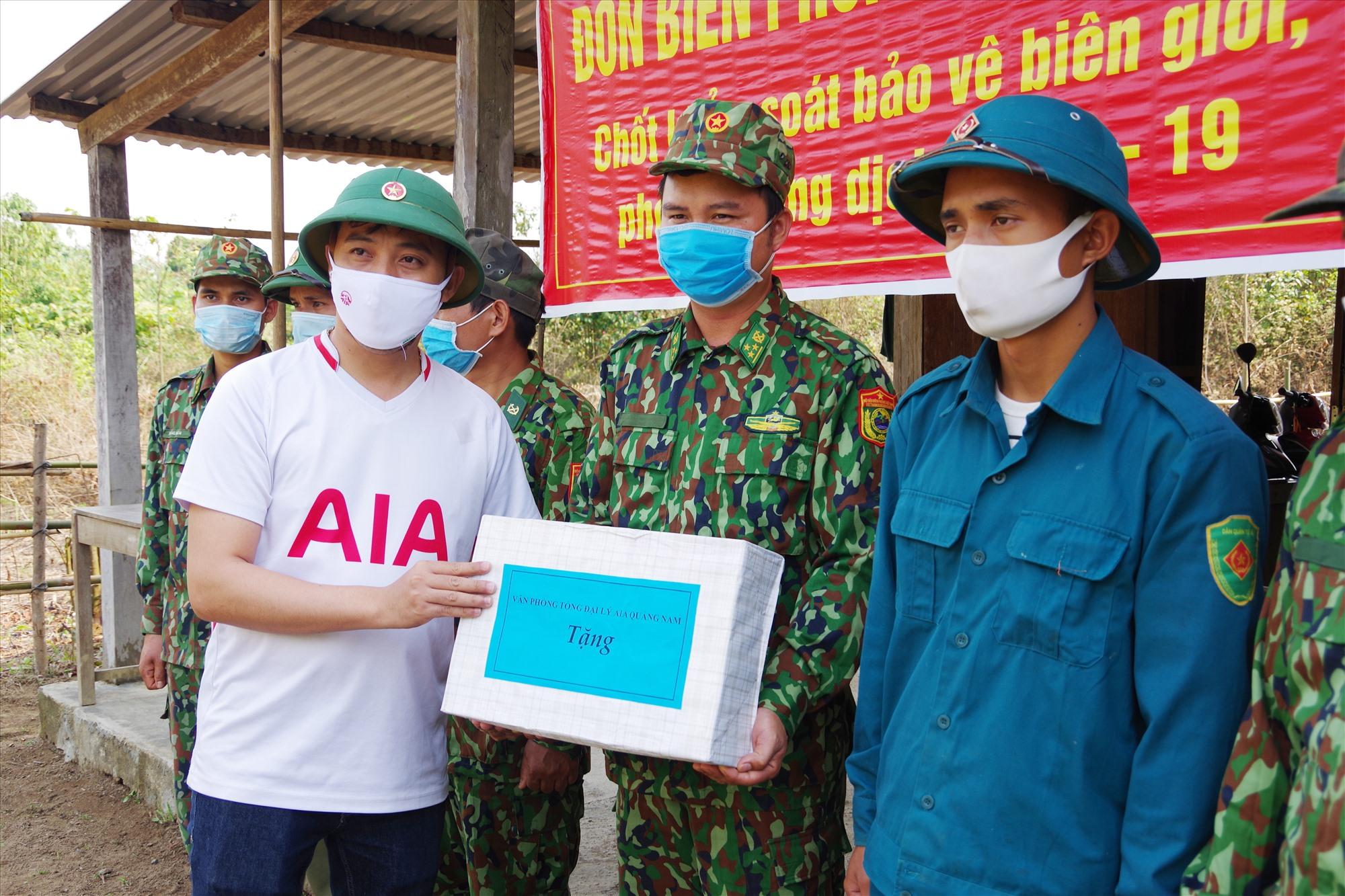 Đại diện Tổng đại lý AIA Quảng Nam tặng quà lực lượng làm nhiệm vụ tại các chốt biên giới. Ảnh HỒNG ANH