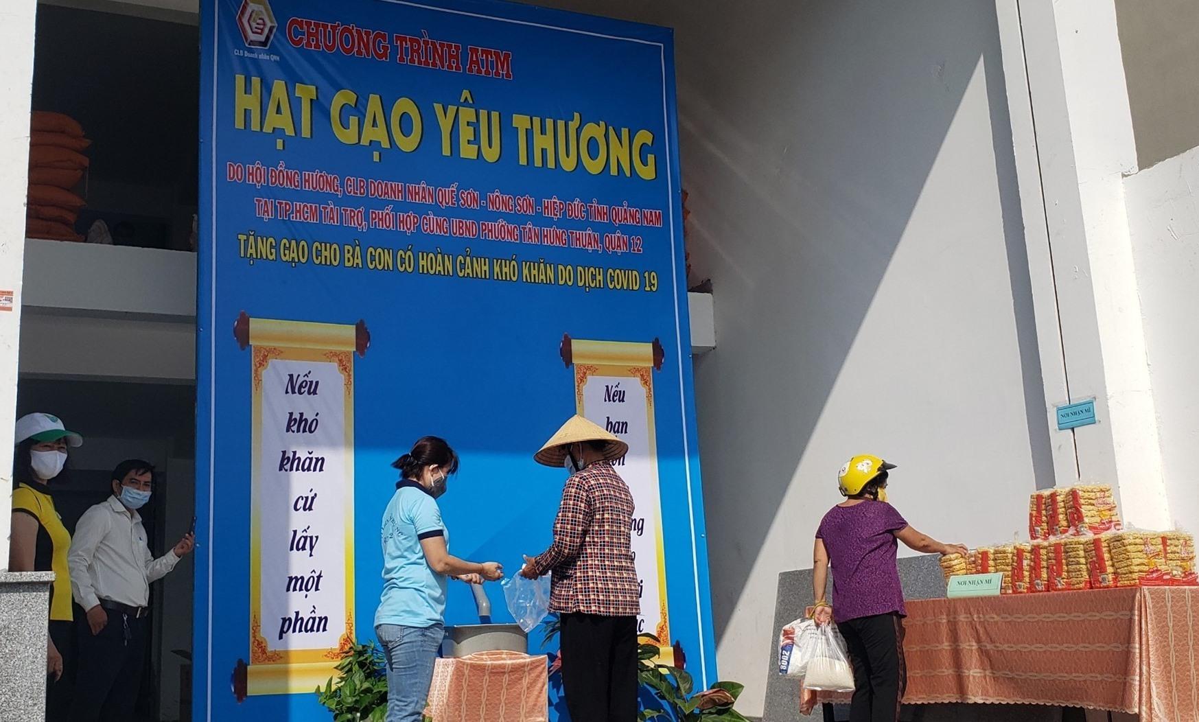 Người dân nhận gạo từ ATM Hạt gạo yêu thương. Ảnh: PHÚC HOÀNG