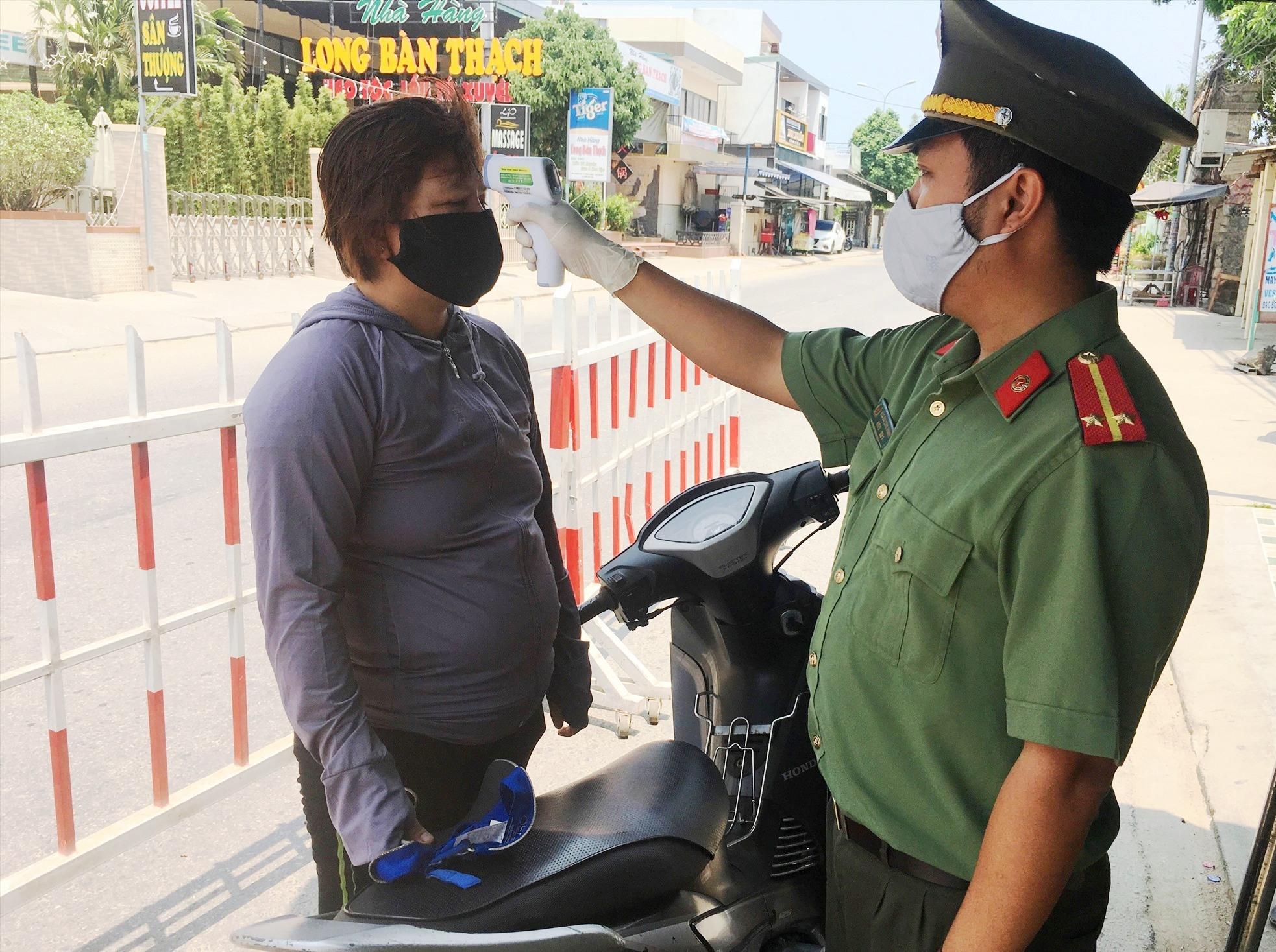 Lực lượng chức năng tại các chốt kiểm soát dịch bệnh thực hiện việc đo thân nhiệt đối với người dân khi vào địa bàn Duy Xuyên.