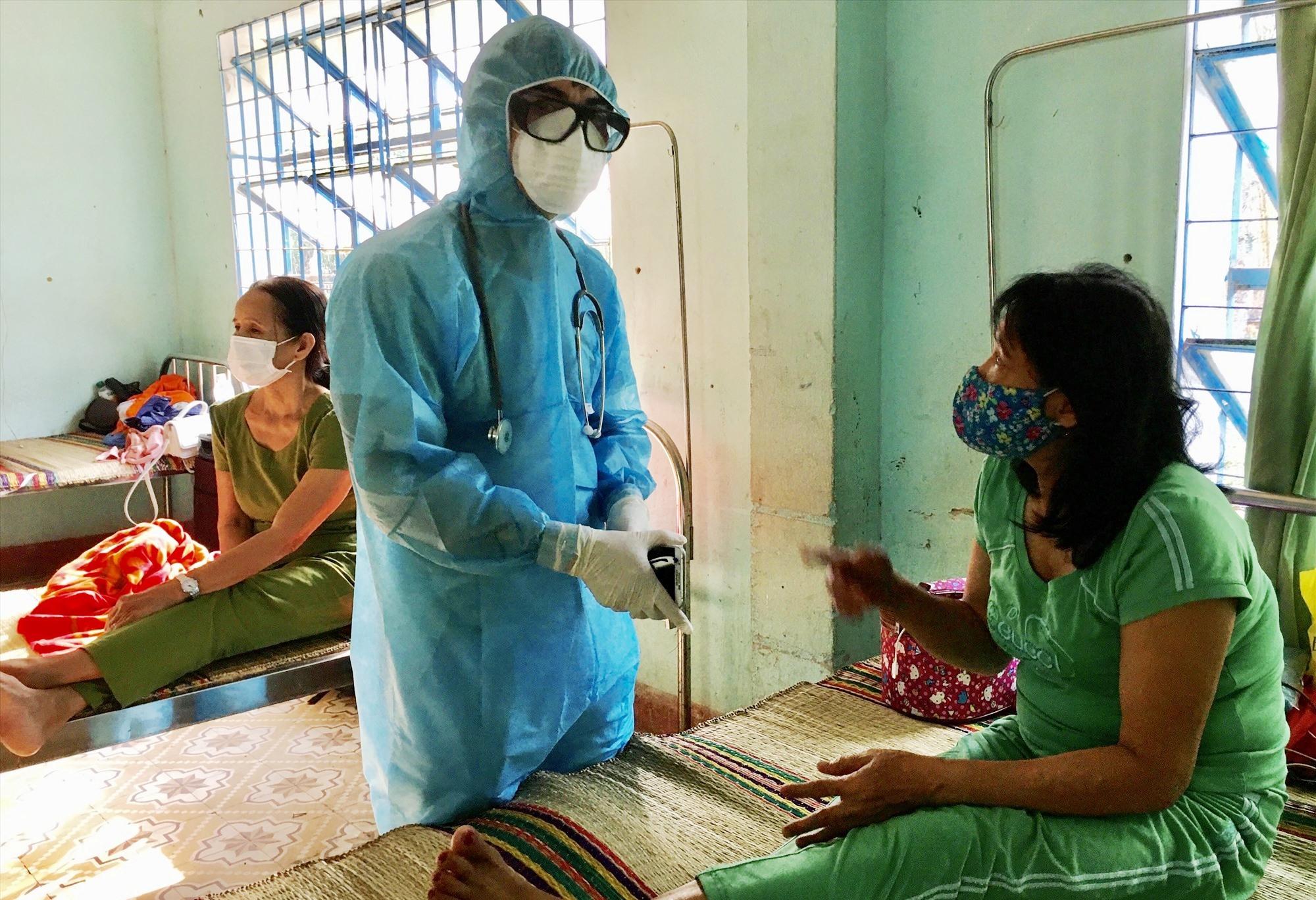 Cán bộ Trung tâm Y tế huyện Phú Ninh thăm hỏi người dân tại khu cách ly tập trung. Ảnh: Đ.C