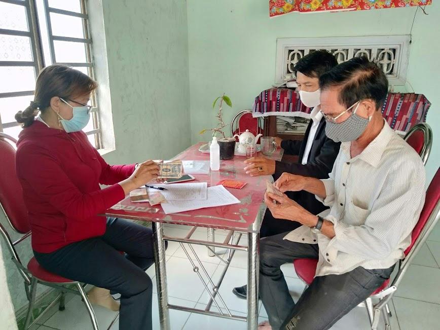 Nhân viên Bưu điện huyện Thăng Bình chi trả trợ cấp thương binh cho gia đình ông Trương Thanh Sơn ở xã Bình Phục.Ảnh: T.T