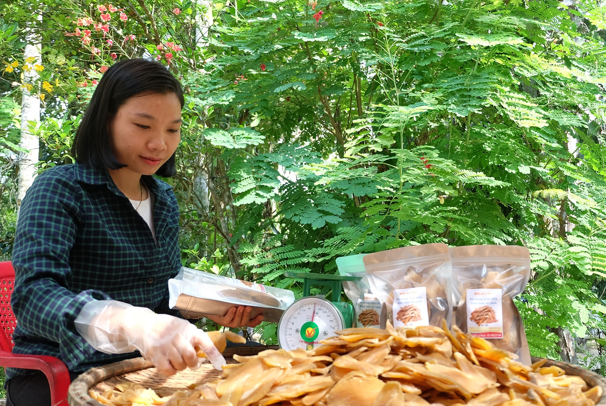Chị Thuận đang đóng gói bao bì cho món khoai dẻo. Ảnh: M.L