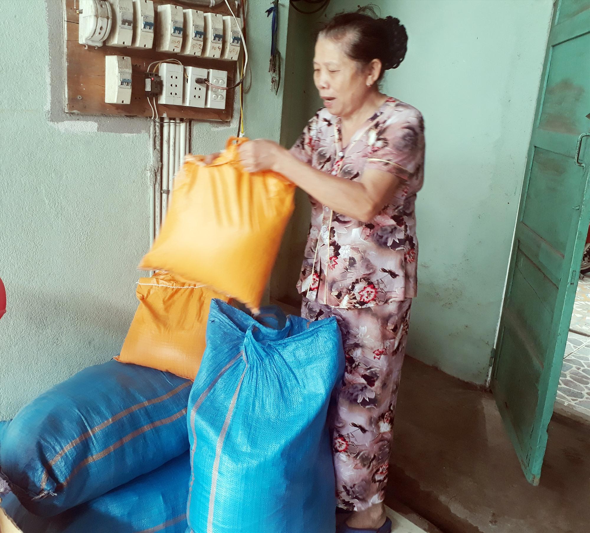 Bà Nguyễn Thị Nhạn chuẩn bị các phần gạo tặng người khó khăn. Ảnh: HUYỀN CHI