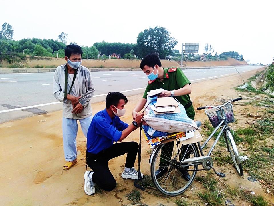 Bạn  Nguyễn Triệu Vĩ và chiễn sĩ công an hỗ trợ người dân khi đi qua chốt kiểm soát lên cao tốc Quảng Ngãi – Đà Nẵng. Ảnh: THÁI CƯỜNG