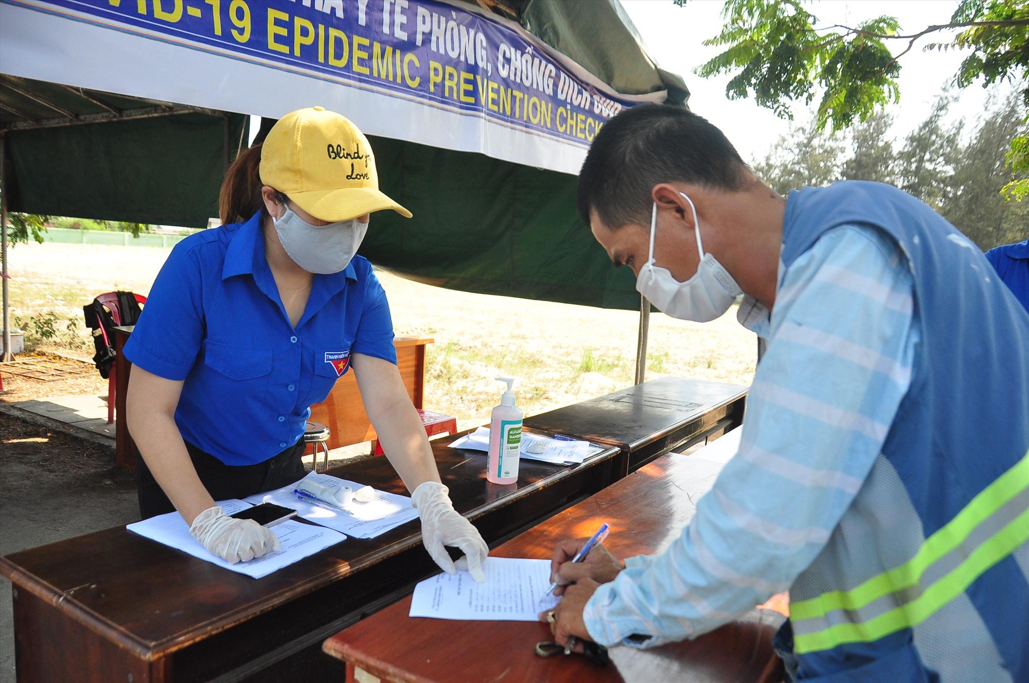 Thanh niên xung kích xã Điện Thắng Bắc (thị xã Điện Bàn) hướng dẫn người dân khai báo y tế tại chốt kiểm soát trên đường ĐT603B. Ảnh: VINH ANH