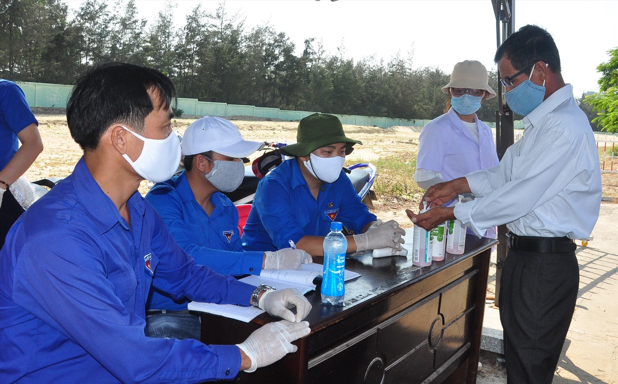 Người dân được hướng dẫn vệ sinh bằng dung dịch sát khuẩn trước khi đến bàn khai báo y tế. Ảnh: VINH ANH