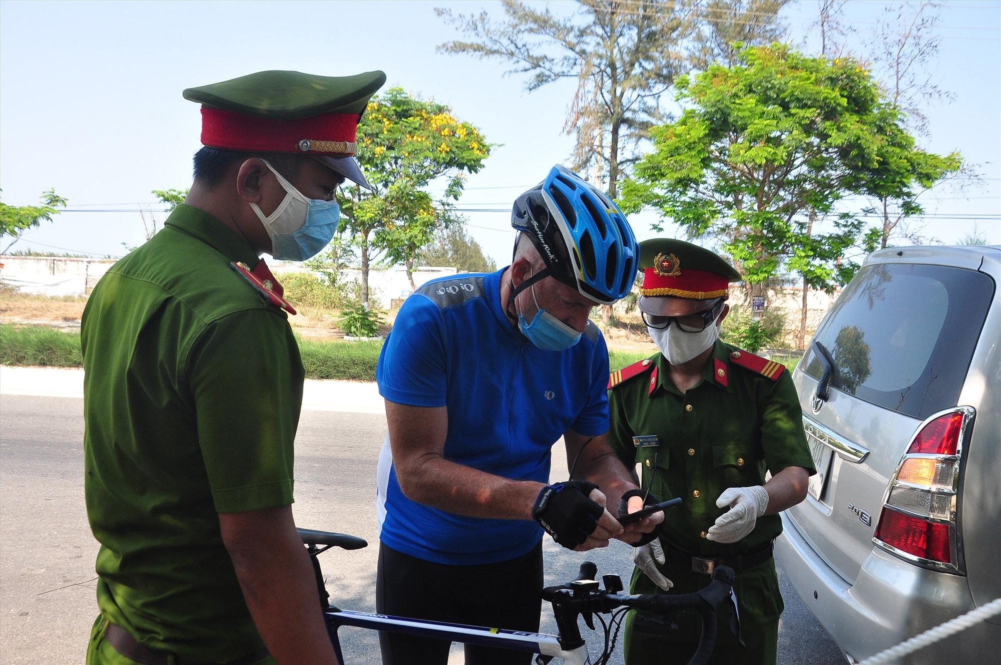 Tại chốt kiểm soát phía bắc trên đường ĐT603B, lực lượng làm nhiệm vụ đang kiểm tra một người ngoại quốc lưu thông bằng xe đạp từ hướng Đà Nẵng vào Hội An. Ảnh: V.A