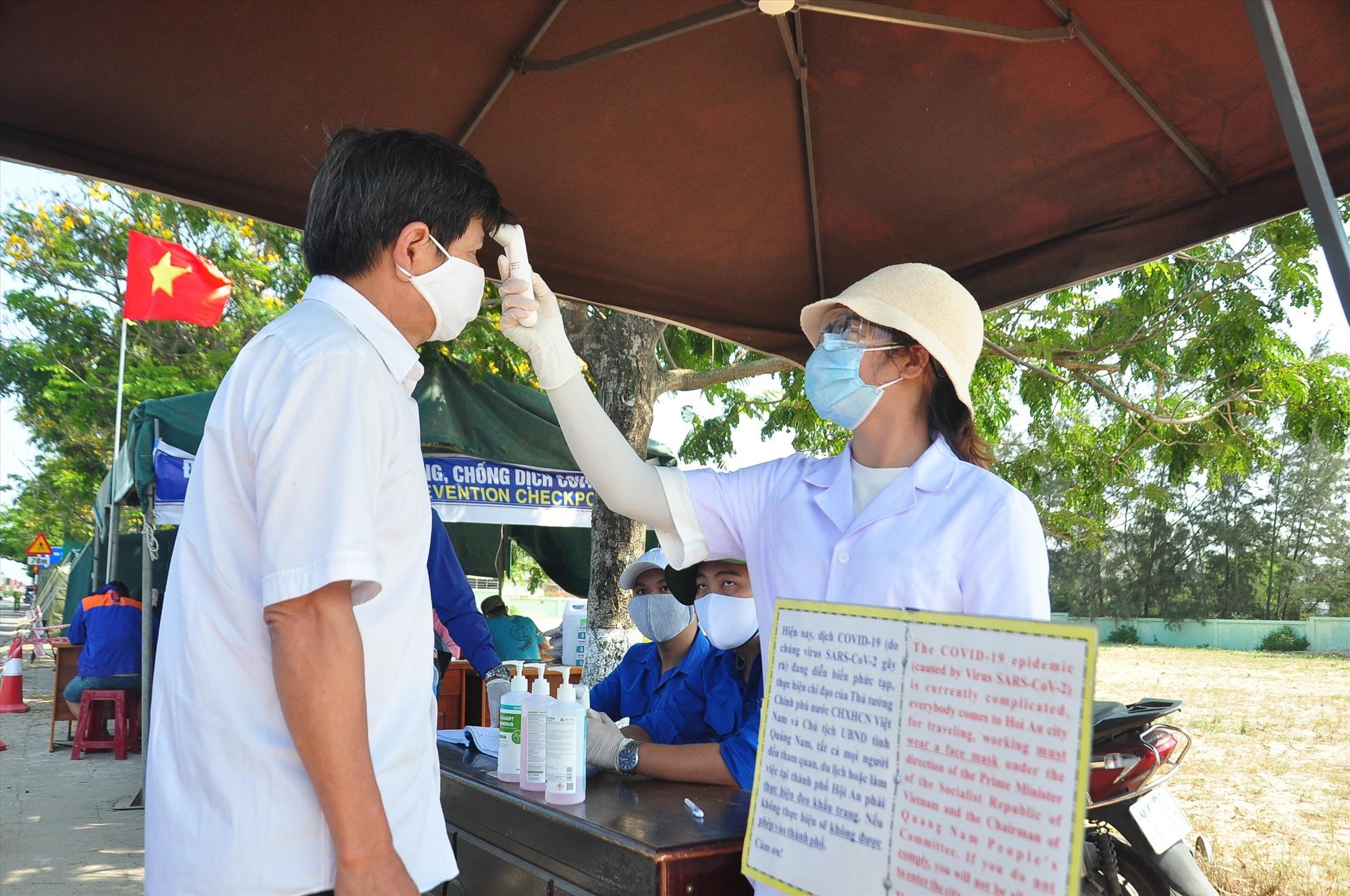 Người dân được đo thân nhiệt trước khi làm thủ tục khai báo y tế tại các chốt kiểm soát. Ảnh: V.A