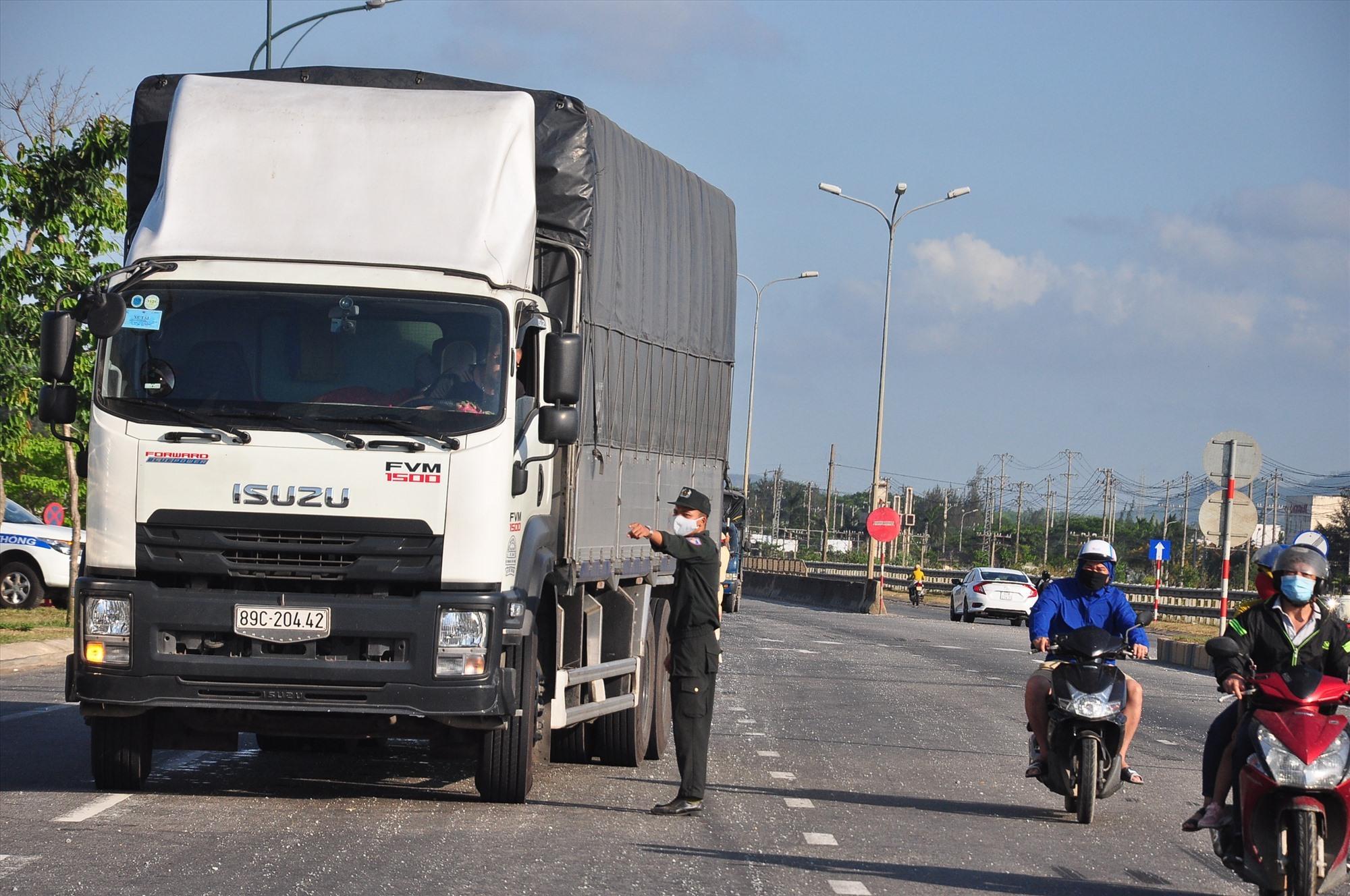 Giữa cái nắng chói chang, một chiến sĩ cảnh sát cơ động đang hướng dẫn tài xế xe tải chấp hành việc kiểm soát dịch bệnh Covid-19 tại chốt kiểm soát phía nam. Ảnh: V.A