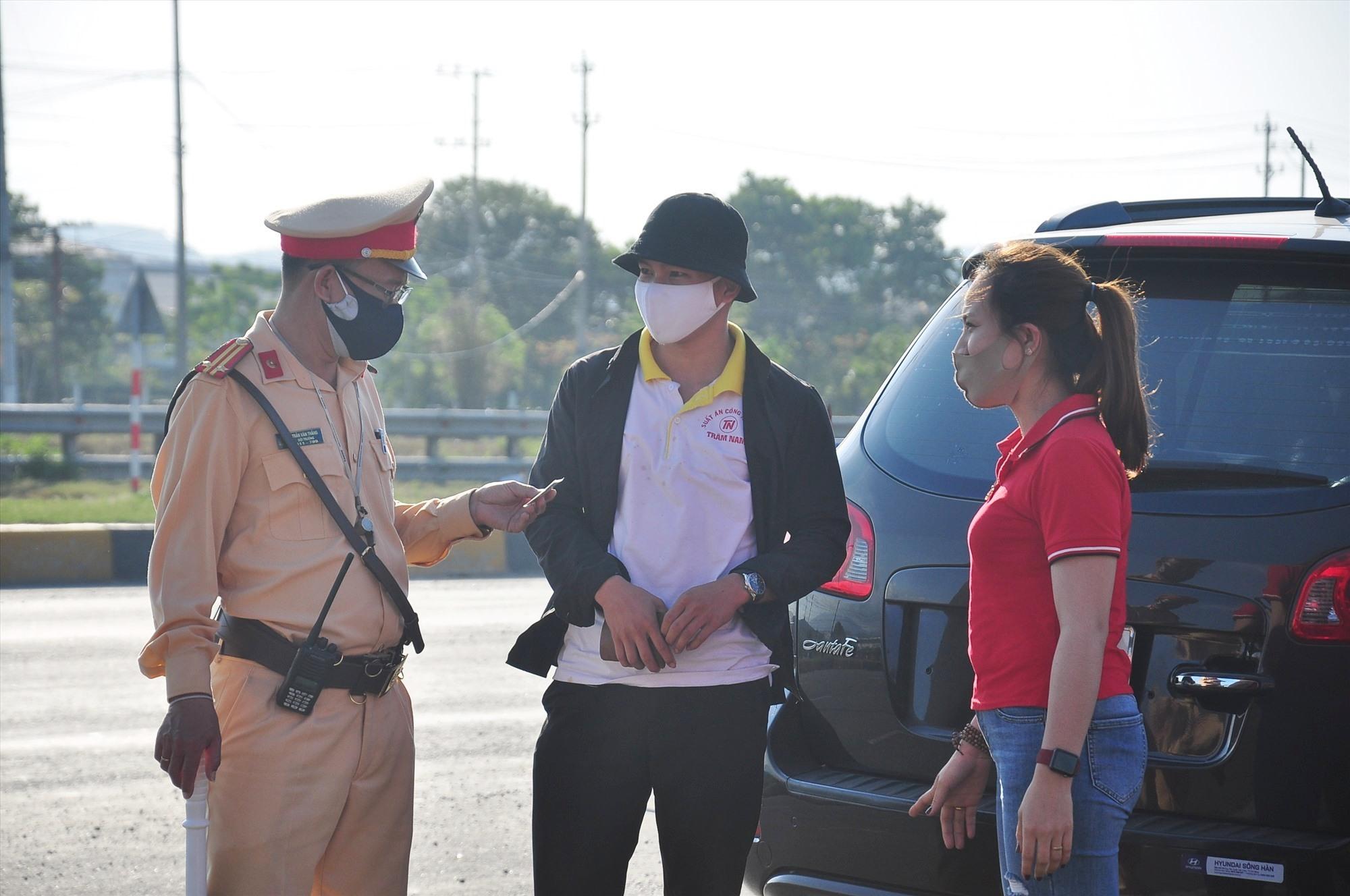 Lực lượng CSGT tham gia điều tiết giao thông, hướng dẫn người dân chấp hành quy định về khai báo y tế. Ảnh: V.A