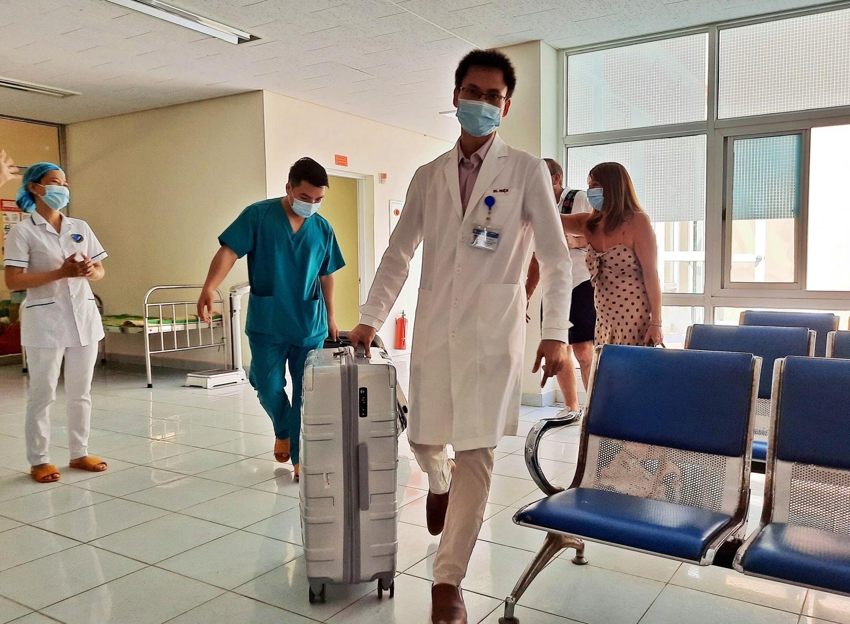 Các y bác sĩ khu cách ly phụ giúp vợ chồng người Anh mang hành lý lên xe. Ảnh: ĐẠO QUÂN