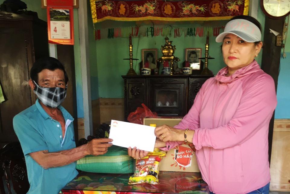 Đại diện Ủy ban MTTQ Việt Nam xã Duy Phước trao tiền và quà hỗ trợ cho người bán vé số trên địa bàn xã.