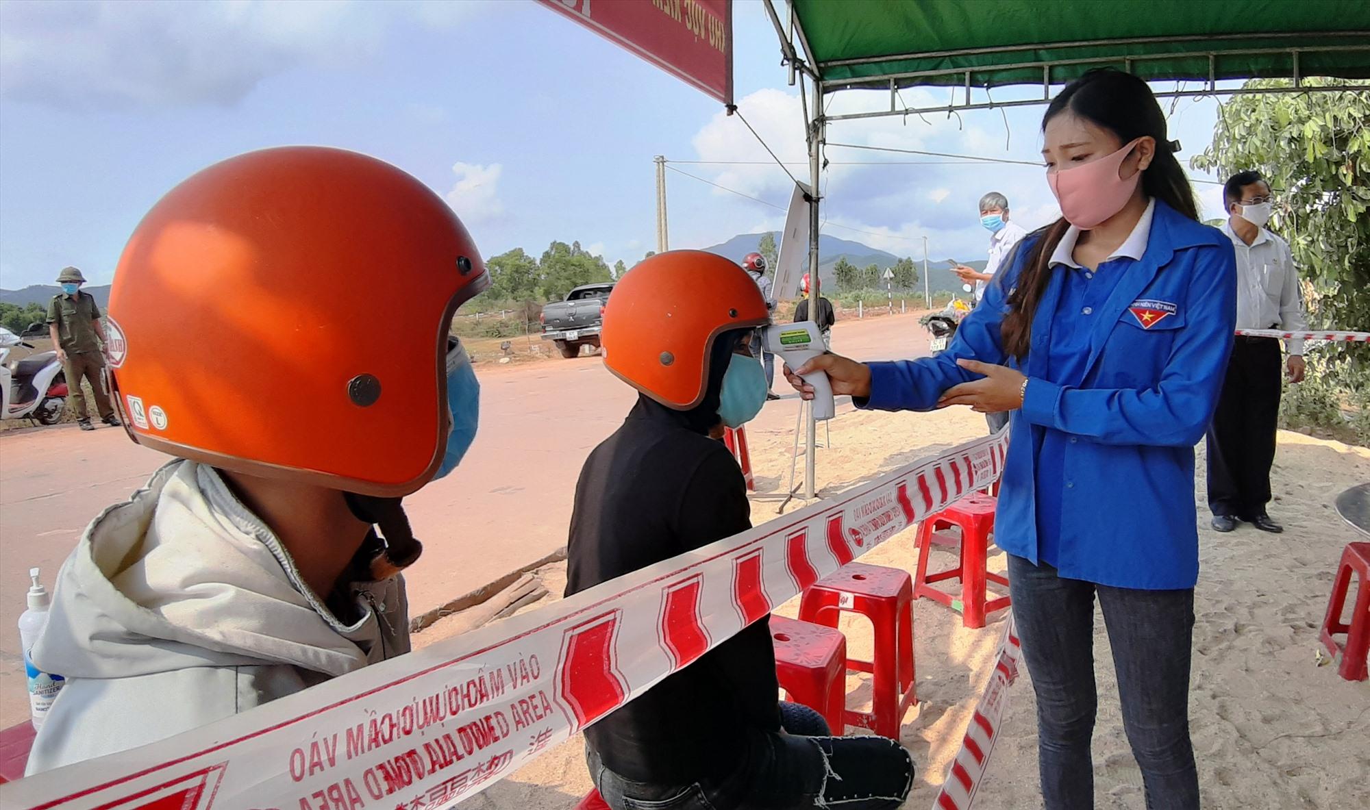 Cơ quan chức năng huyện Duy Xuyên đo thân nhiệt người dân mỗi khi ra vào địa bàn.    Ảnh: H.N