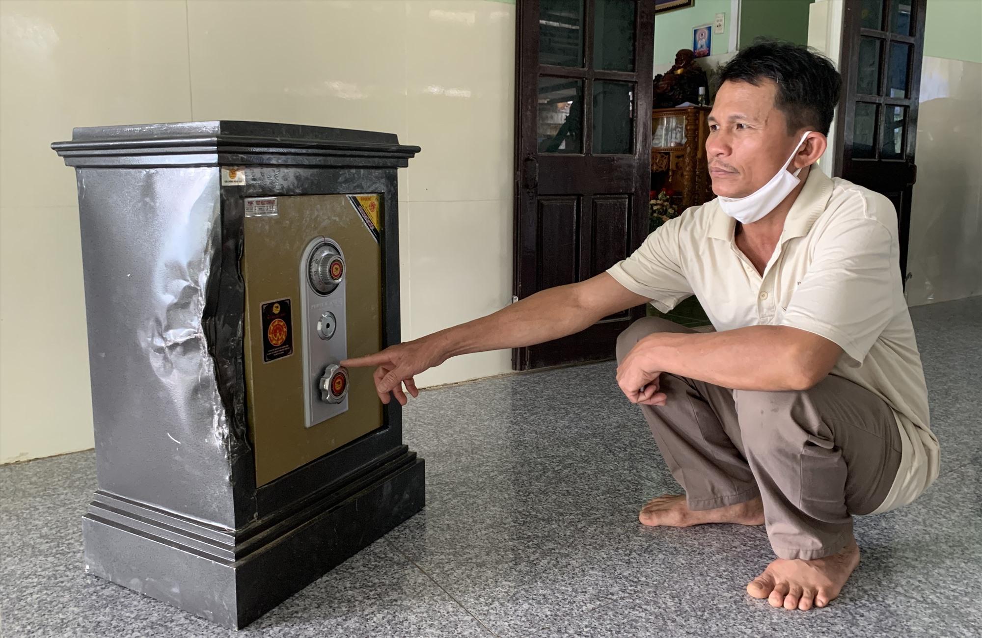 Anh Đỗ Văn Hùng bên cái két sắt đã bị các tên trộm phá. Ảnh: PHAN VINH