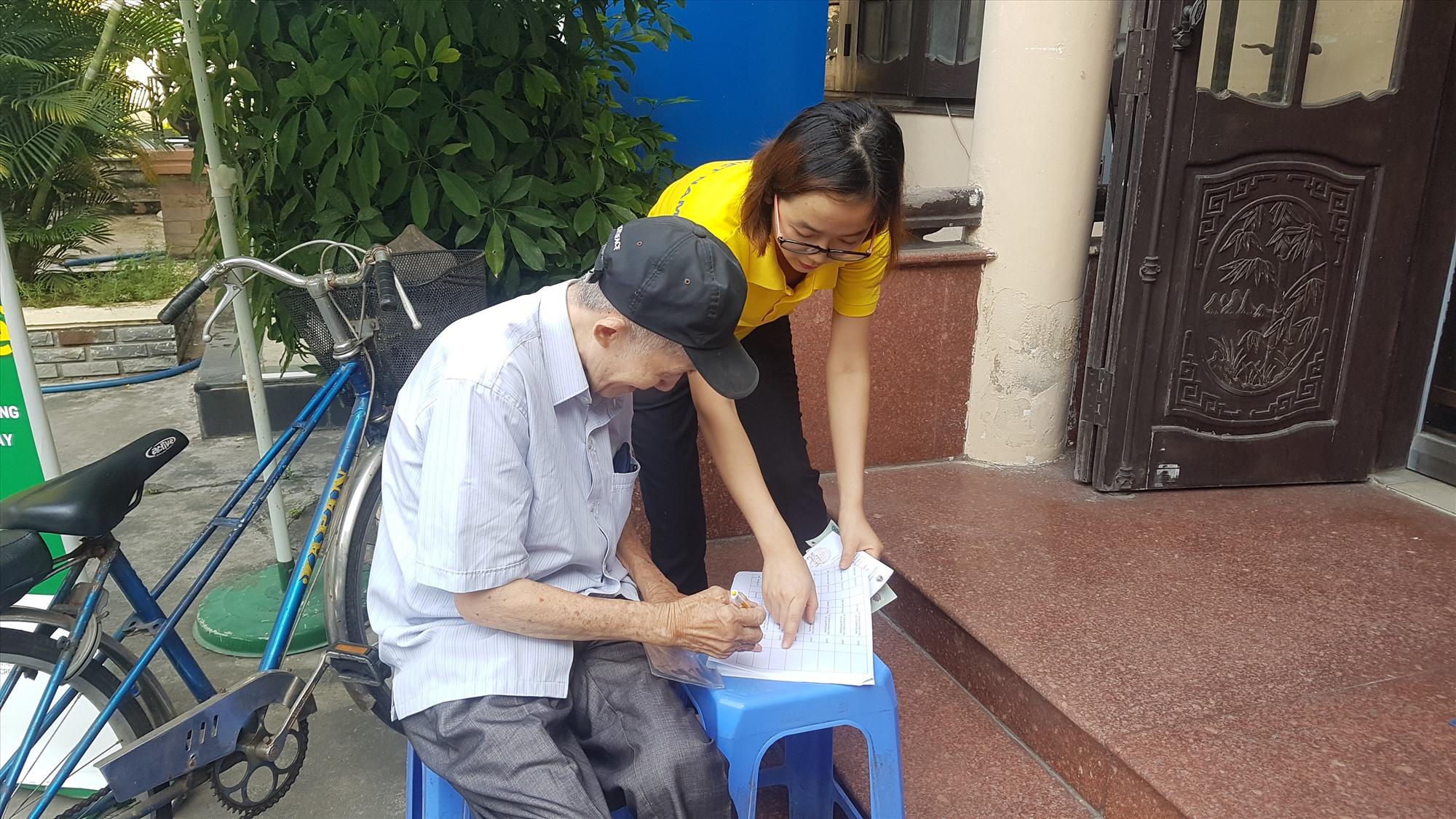 Người khuyết tật đi lại khó khăn được hỗ trợ nhận tiền hỗ trợ. Ảnh: D.L