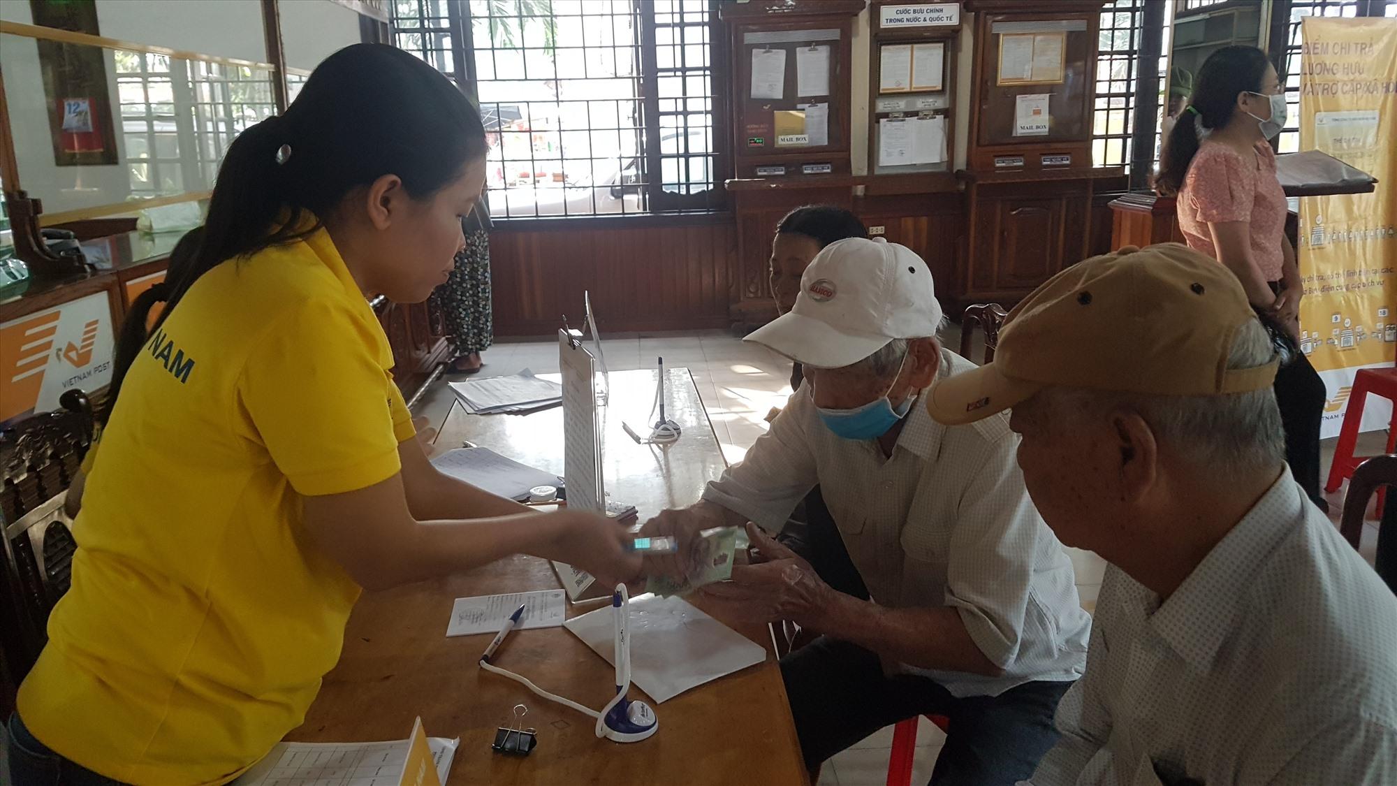 Người có công nhận chi trả chế độ tại Bưu điện TP.Hội An. Ảnh: D.L