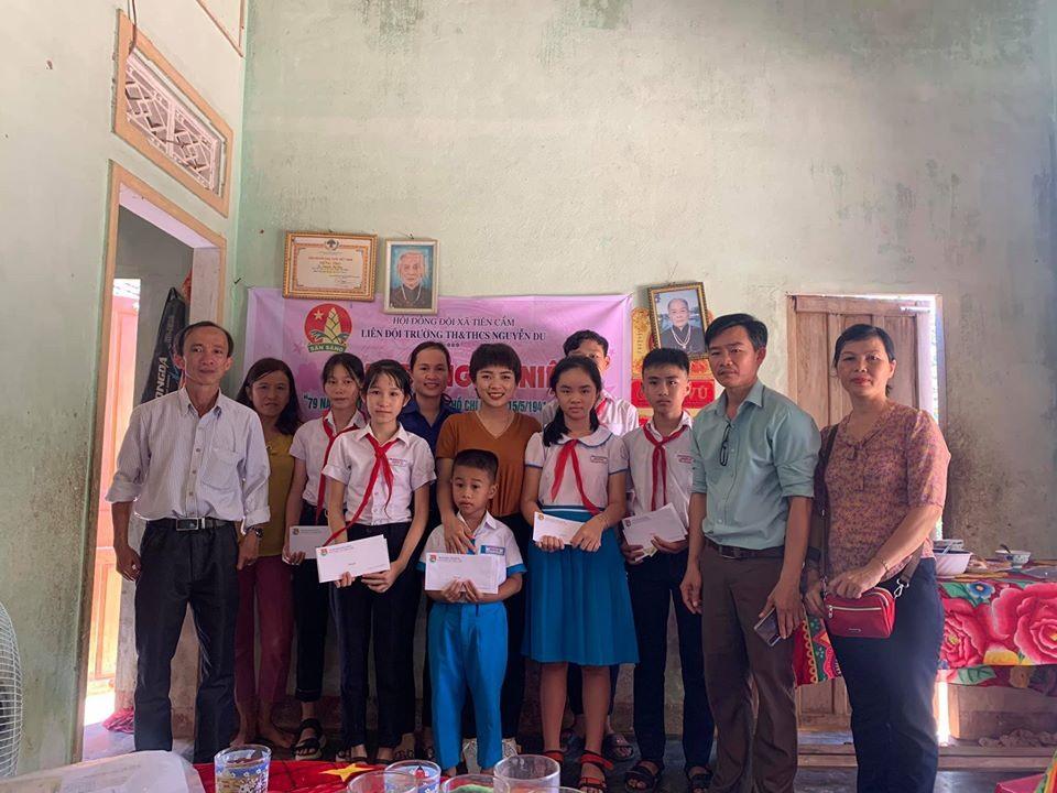 Chị Tố Nga cùng Đoàn xã và Hội đồng đội trường tiểu học, THCS ở xã Tiên Cẩm trao quà cho học sinh. Ảnh: S.S