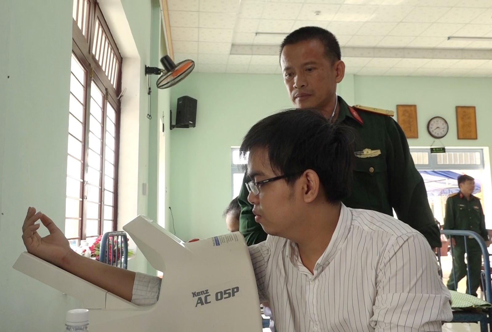 Thiếu tá Lê Văn Đào khám sức khỏe nghĩa vụ quân sự cho thanh niên năm 2020. Ảnh: V.T