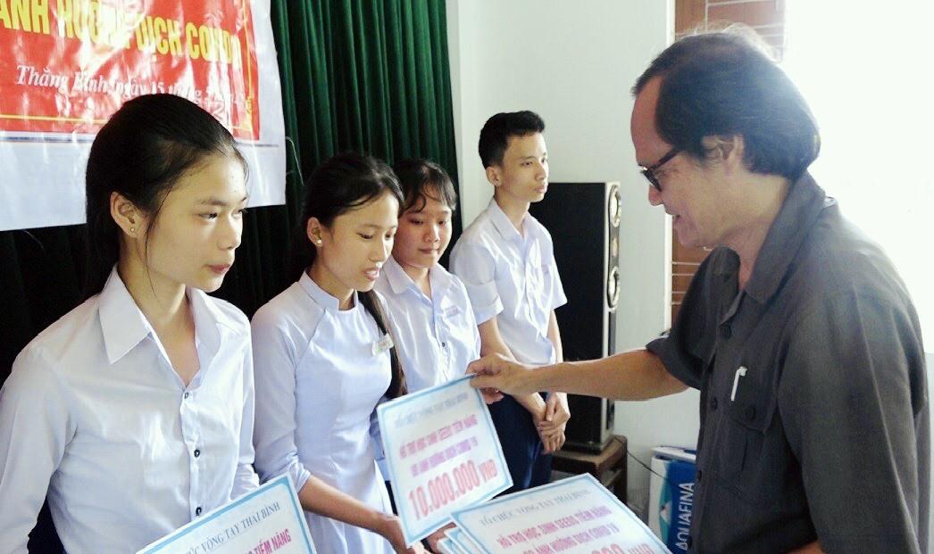 Ông Nguyễn Hữu Hiệp - Chủ tịch Hội Khuyến học huyện Thăng Bình trao học bổng cho học sinh có hoàn cảnh khó khăn. Ảnh: TÂN SƯƠNG