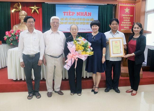 Lãnh đạo huyện Duy Xuyên tặng hoa và bản ghi nhận cho gia đình cố nhạc sĩ.