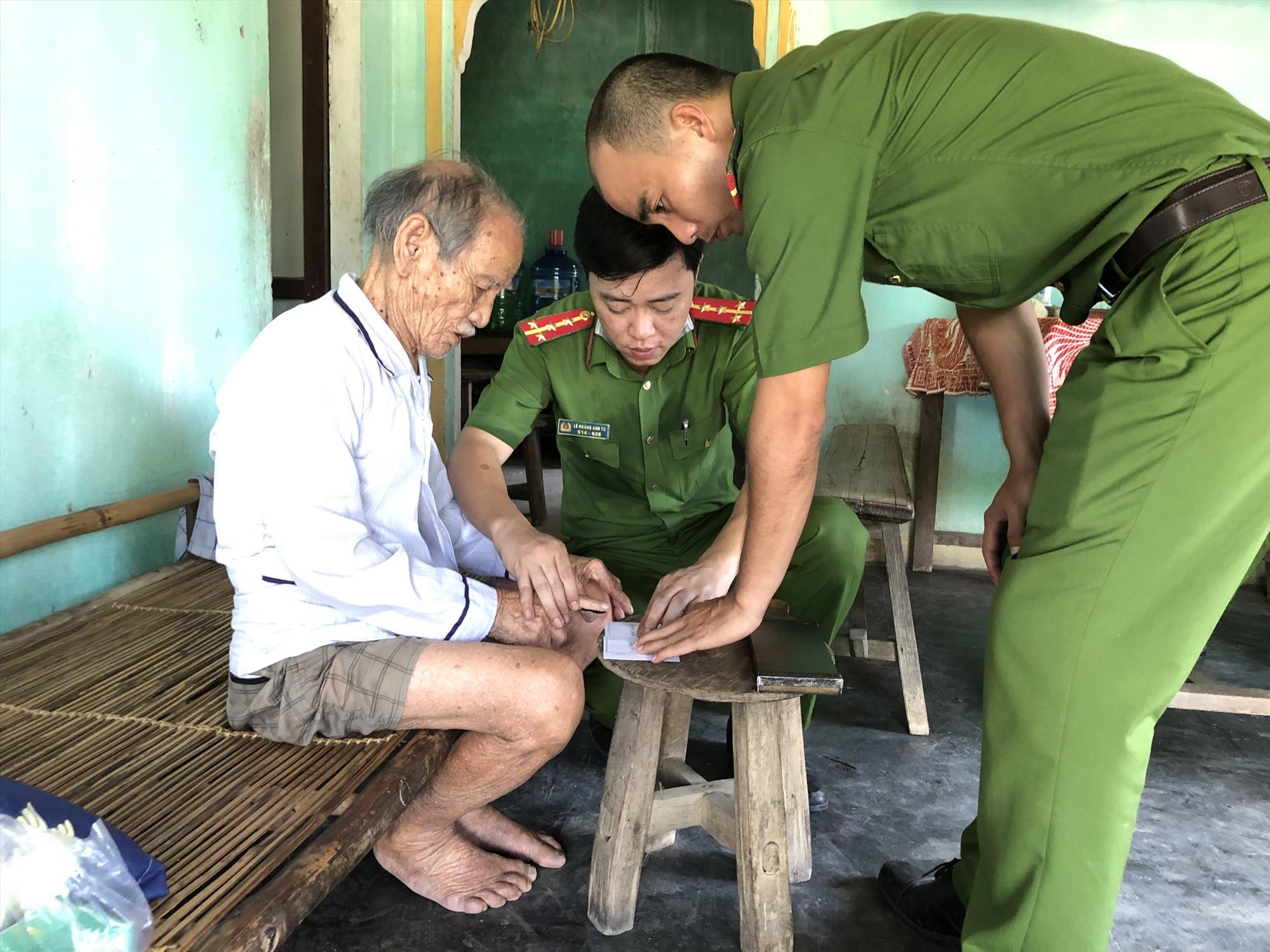Đoàn viên thanh niên Chi đoàn Công an huyện Đại Lộc đến tận nơi làm thủ tục cấp chứng minh nhân dân cho người cao tuổi. Ảnh: C.A