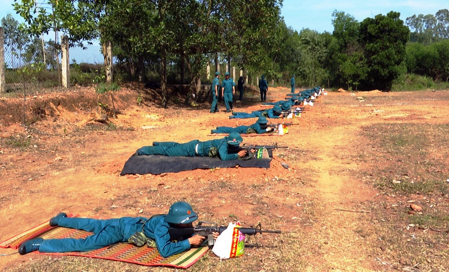 Các chiến sĩ dân quân thực hiện huấn luyện bài bắn súng trên thao trường.