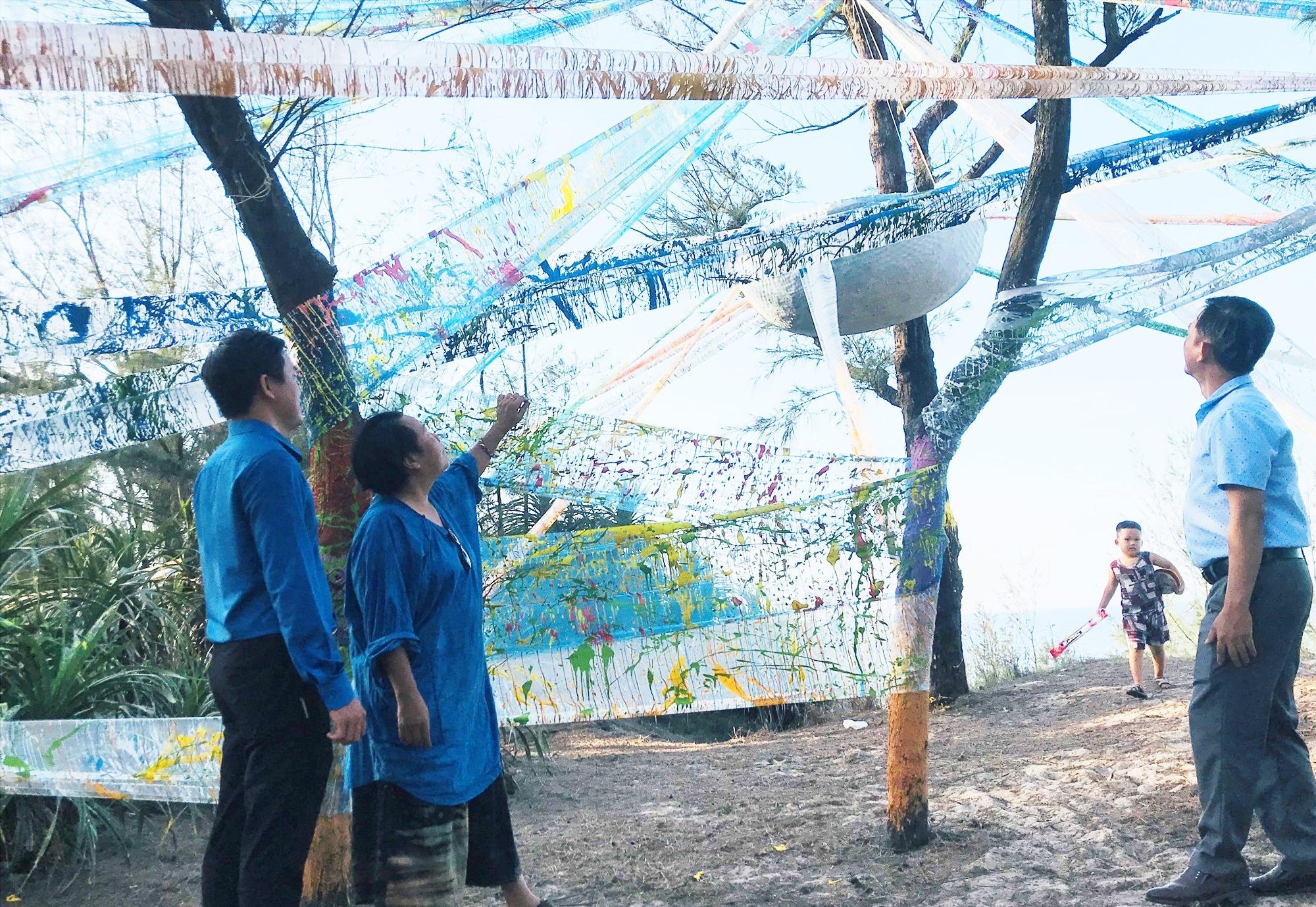 """Họa sĩ Trần Thị Thu (Hà Nội) trao đổi với lãnh đạo xã Tam Thanh về tác phẩm """"ra khơi"""". Ảnh: C.N"""