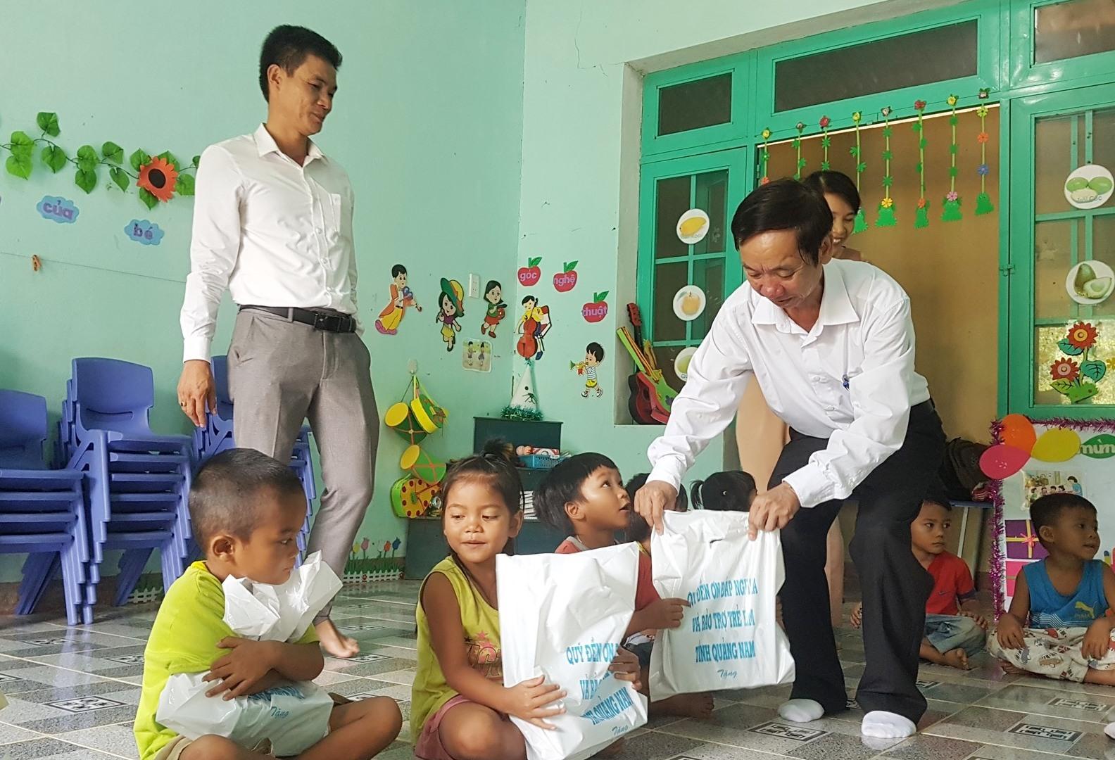 Đồng chí Võ Hồng tặng quà cho trẻ mẫu giáo. Ảnh: D.L