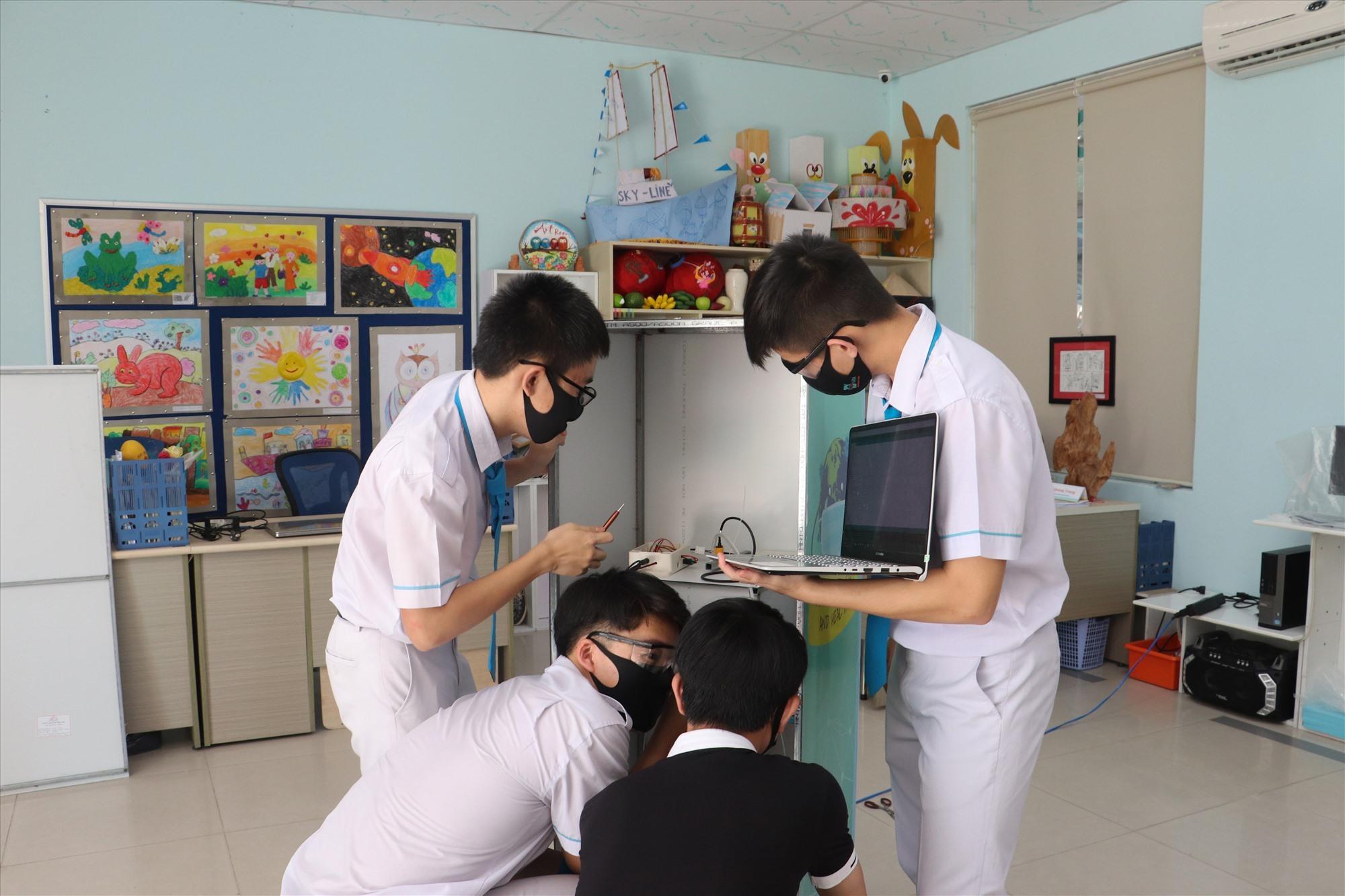 Nhóm học sinh Sky-Line chế tạo máy rửa tay xit khuẩn tự động. Ảnh Q.L